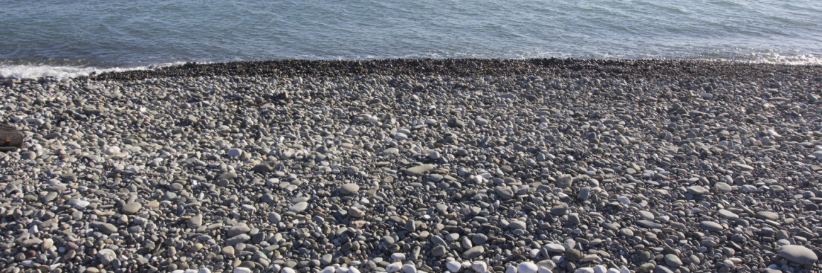 The sign Success made from white pebbles on pebble beach on the sea